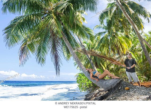 Relaxing woman lies on the coconut palm tree next is a man with a fan on a tropical beach. Young beautiful woman lying on the palm tree on sea shore