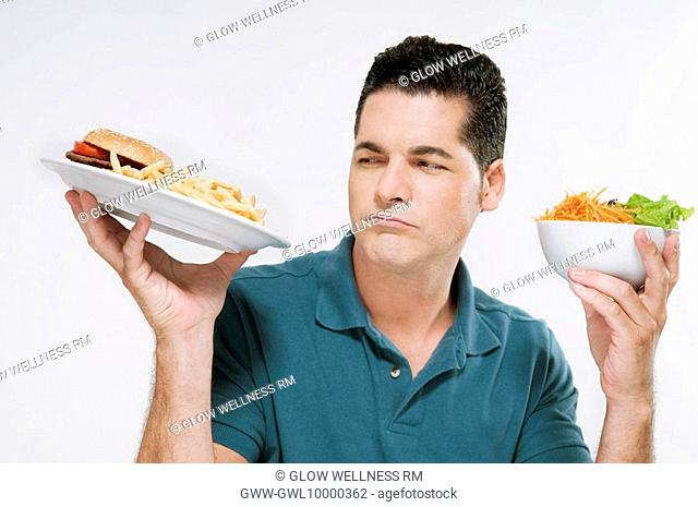 Man choosing between a hamburger plate and a salad bowl