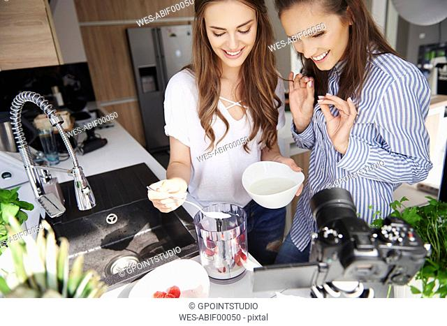 Food bloggers filming theirselves with blender in kitchen