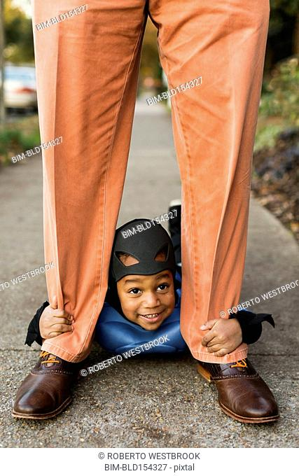 African American boy trick-or-treating with father on Halloween