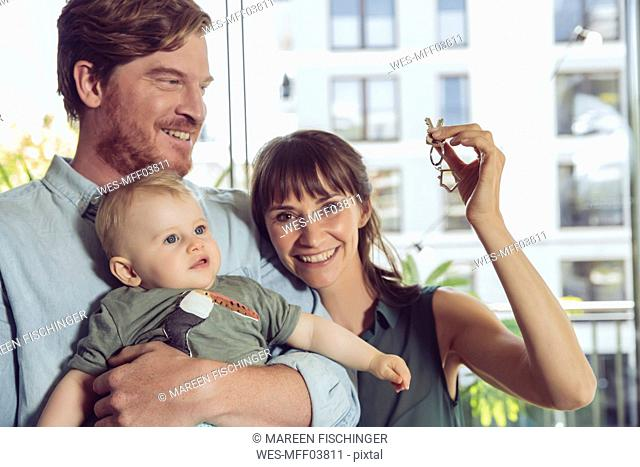 Happy couple with baby holding house key