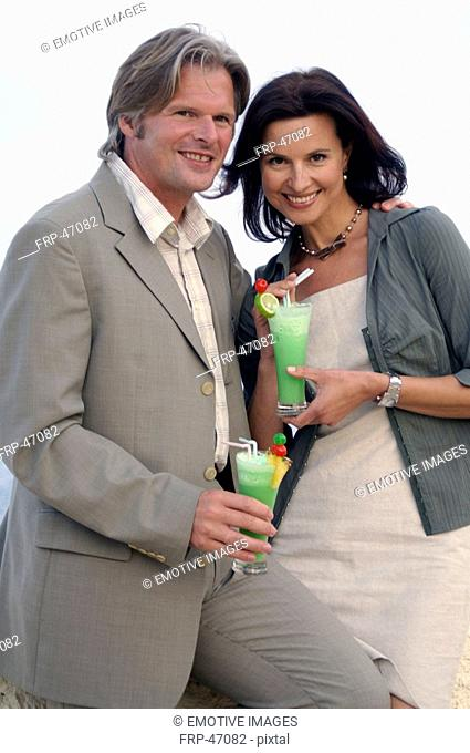 Couple with cocktails at the sea