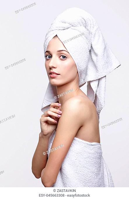 Portrait of beautiful girl. Young woman with bath towel on the head. Female covered in bath towel posing on gray background