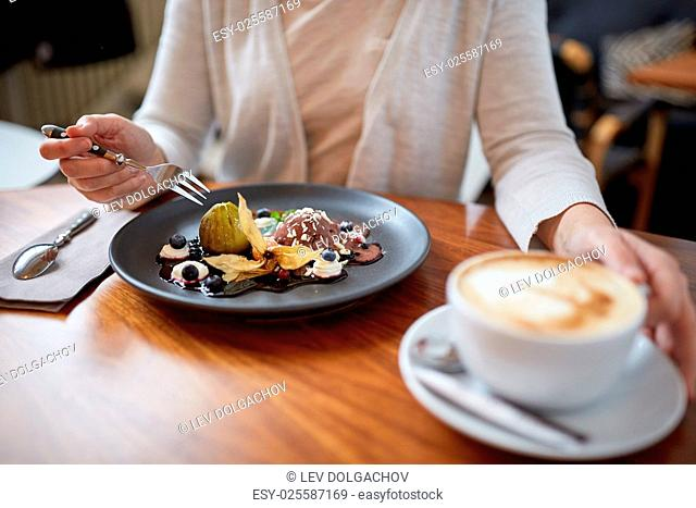 food, new nordic cuisine and people concept - woman eating chocolate ice cream dessert with blueberry kissel, honey baked fig and greek yoghurt with coffee at...