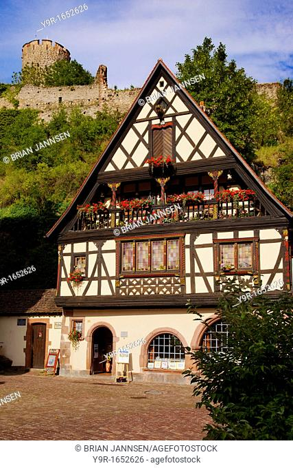 Home and shop in Kaysersberg, along the Wine route with ruins of chateau beyond, Alsace Haut-Rhin France