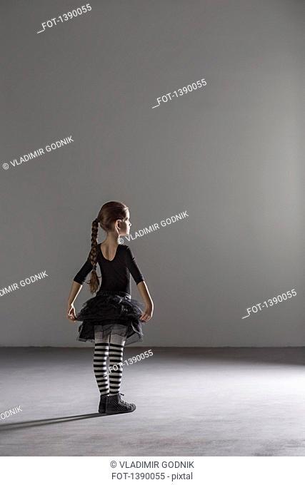 Full length rear view of girl in ballet costume in studio