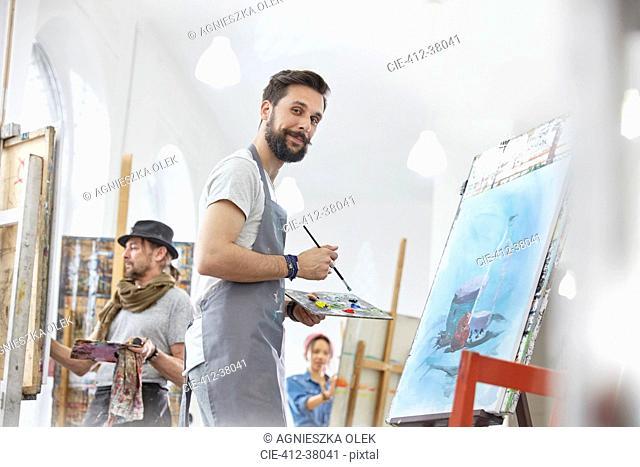 Portrait confident male artist painting with palette in art class studio