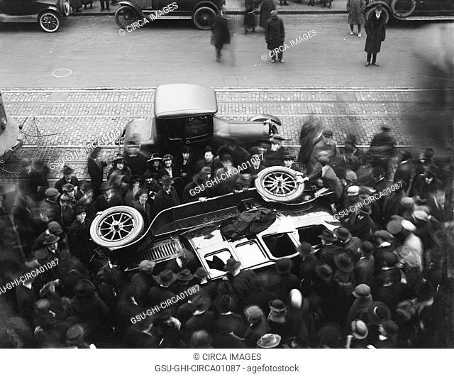 Crowd surrounding overturned automobile, USA, circa 1920