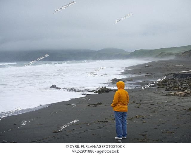 Woman looking out to the storm tossed surf Kodiak Island, Alaska