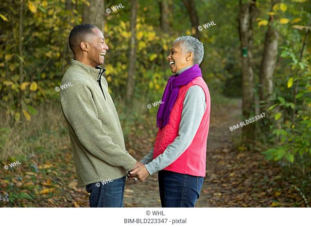 Older couple holding hands in forest