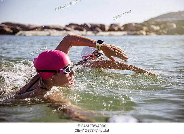 Determined female open water swimmer with smart watch swimming in sunny ocean