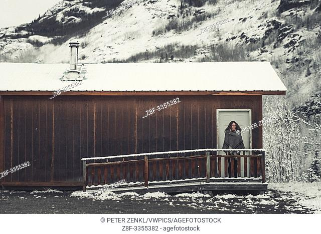 A young Woman is wrapped in a woolen blanket outside of a simple wooden cabin. Yukon Territory, Canada