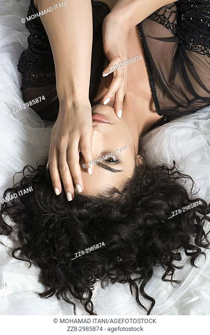 Serious young woman laying down in bed hand covering eye