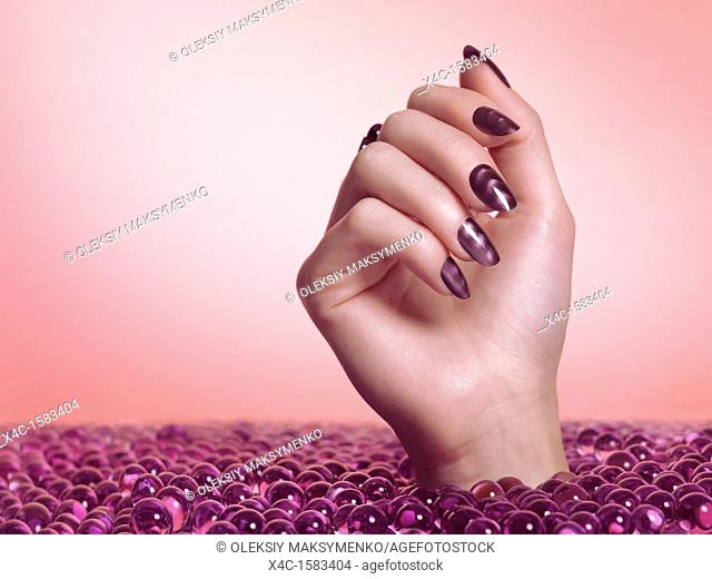 Woman hand with purple nail polish coming out of a sea of candy on pink background