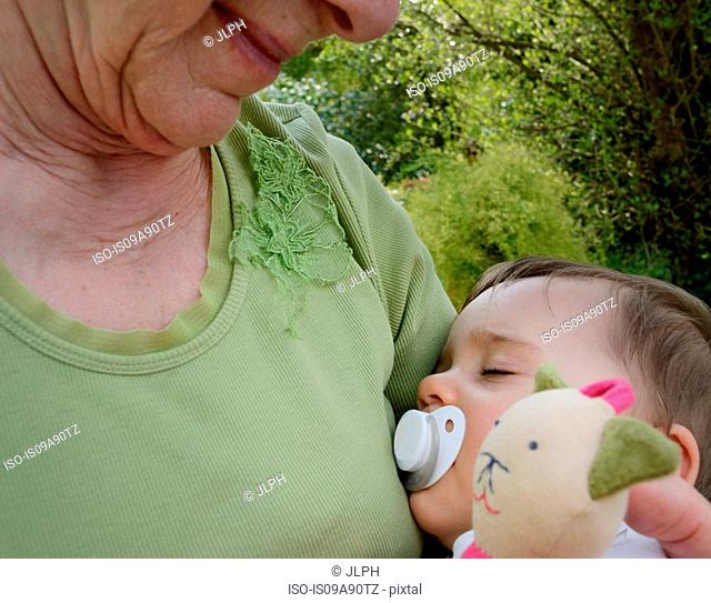 Senior woman holding sleeping granddaughter, close up