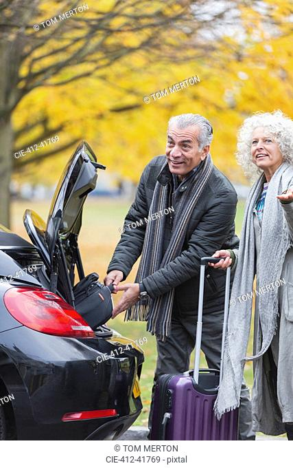 Senior couple removing luggage from car trunk