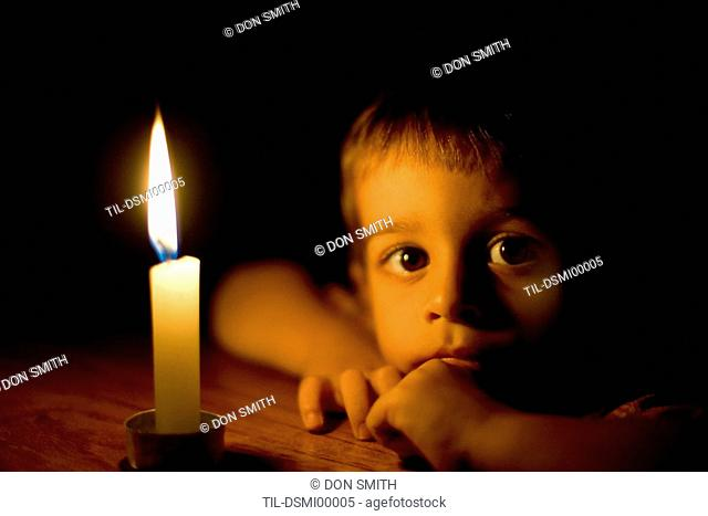 A young boy leaning against a wooden table looking at the camera beside a small candle
