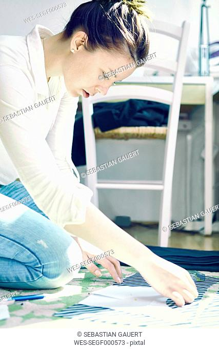 Young woman crouching on the floor at home putting stencil on fabric