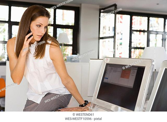 Young woman in office using mobile phone, looking at computer screen