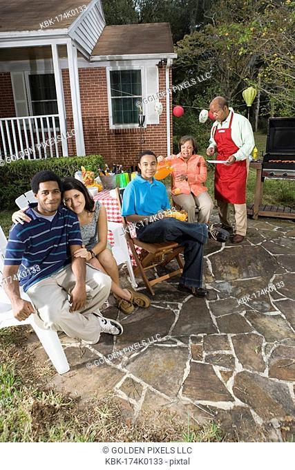 Interracial couple and family enjoying backyard barbeque