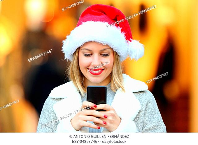 Front view portrait of a happy girl sending smart phone messages in christmas holidays on the street