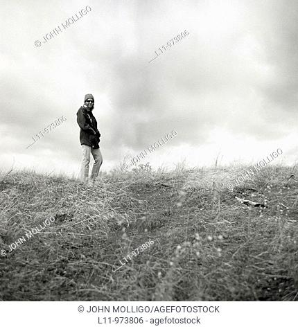 Woman in field on cloudy day