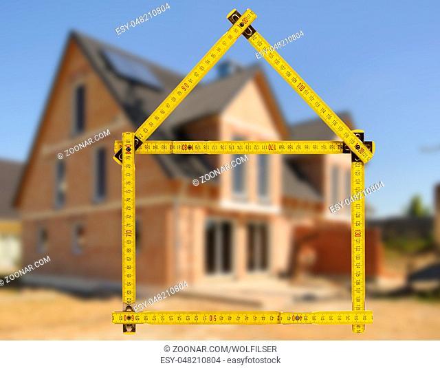 Hausbau und Verkauf mit Meterstab als Symbol