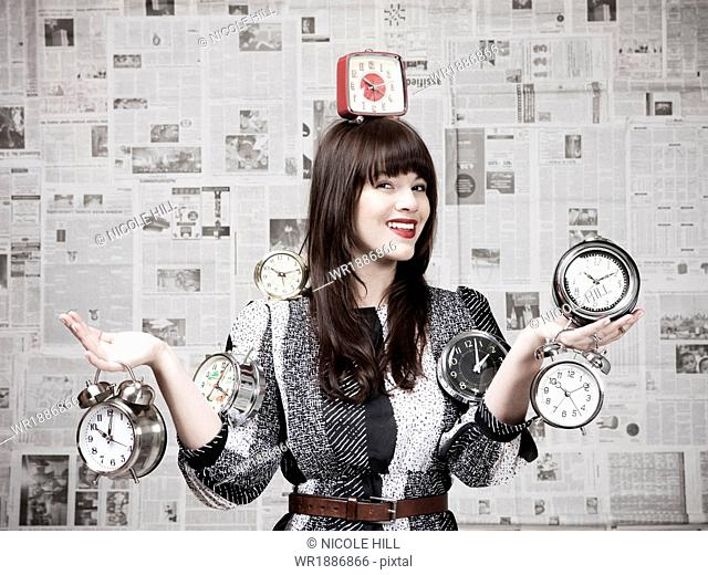 Studio shot of young woman holding alarm clocks