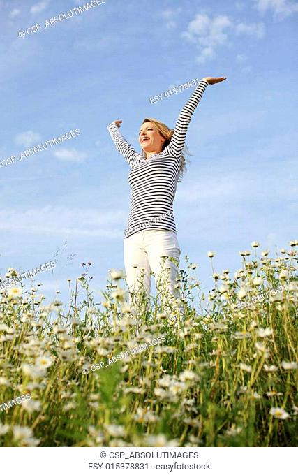 Woman with stretched arms in flower field