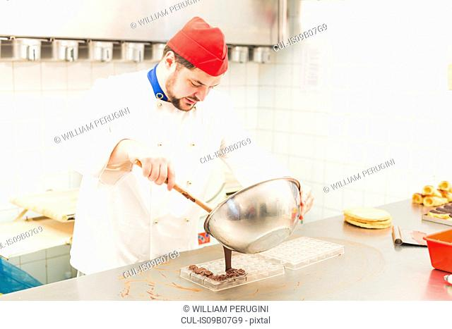Chef pouring chocolate into chocolate mould