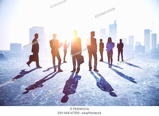 Crowd of businessmen and women standing on abstract city background with sunlight and shadows. Teamwork, success and work concept. Double exposure