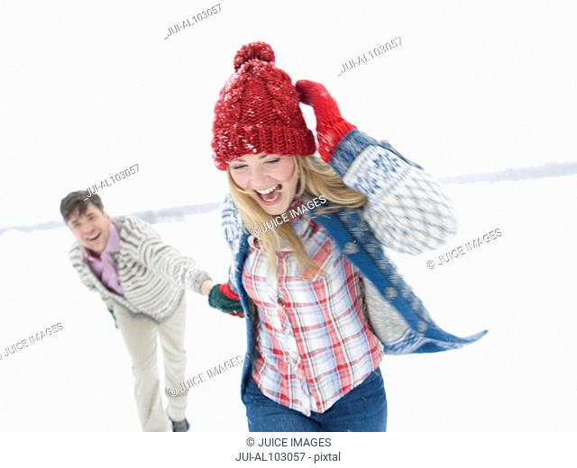 A young couple running through the snow holding hands