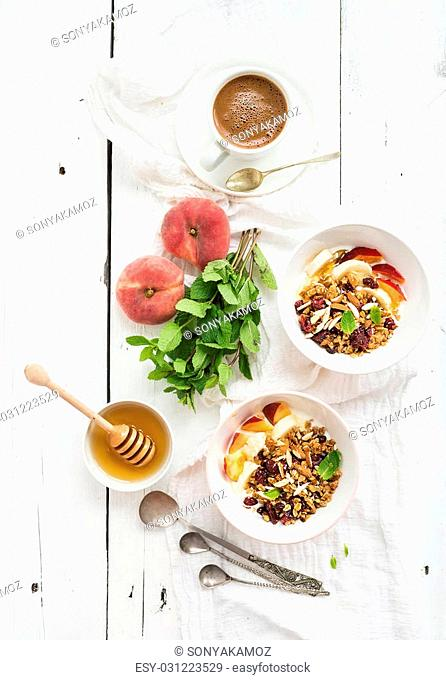 Healthy breakfast. Bowl of oat granola with yogurt, fresh fruit, mint and honey. Cup of coffee, vintage silverware. Top view