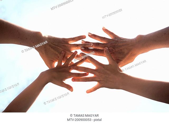 Close up of a family hands together against sunlight, Bavaria, Germany
