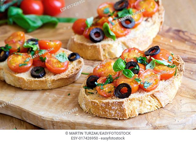 Toasted bread topped with cherry tomatoes, black olives and basil