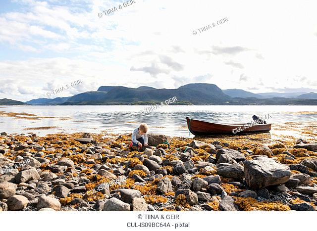 Boy playing amongst rocks by fjord, Aure, More og Romsdal, Norway