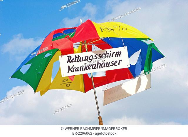 Broken umbrella with sign Rettungsschirm Krankenhaeuser, German for rescue umbrella for hospitals, 10, 000 workers from southern Bavaria demonstrated for a 6