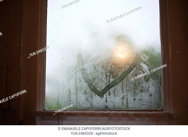 Heart drawn on the window of the house, raining outside