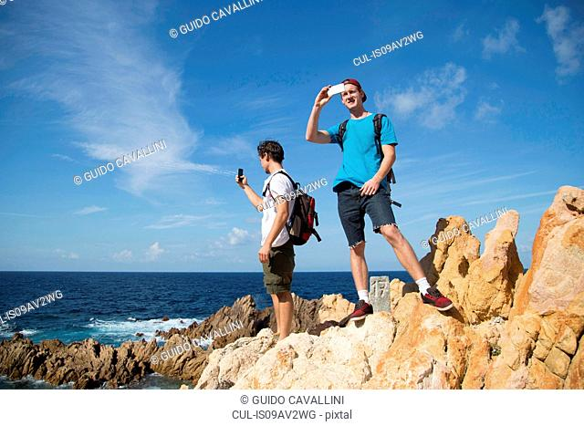 Young men standing on rocks using smartphone to take photograph, Costa Paradiso, Sardinia, Italy