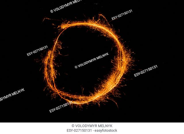 The English letter O made of sparklers on black background