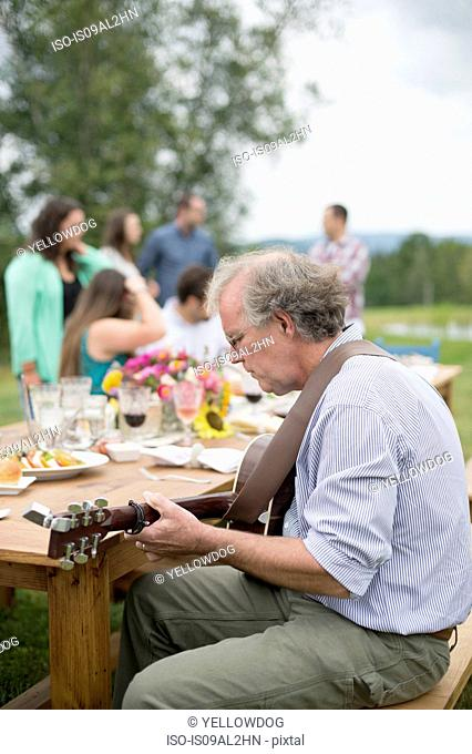 Mature man playing guitar while friends and family talk together after meal, outdoors