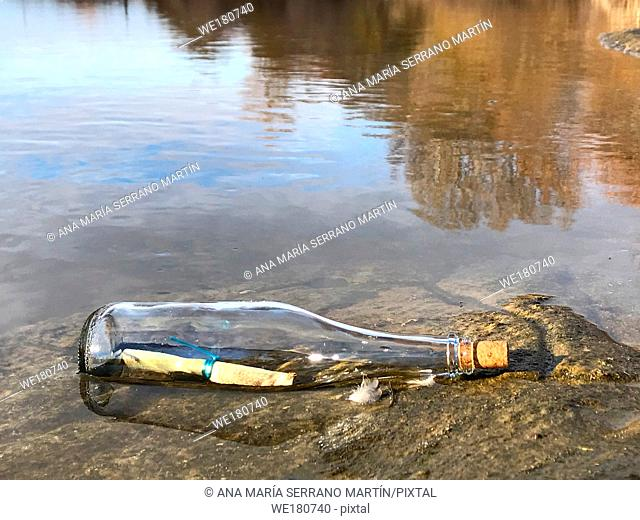 Text message in a crystal bottle in the beach with water and sand