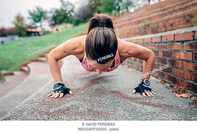 Woman doing pushups on stairs