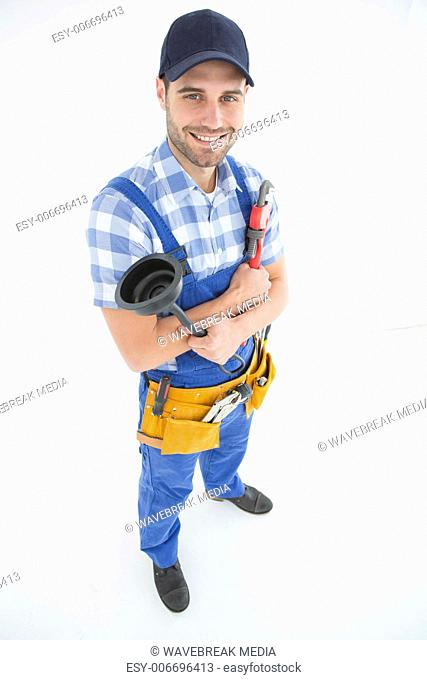 Male plumber holding plunger and wrench