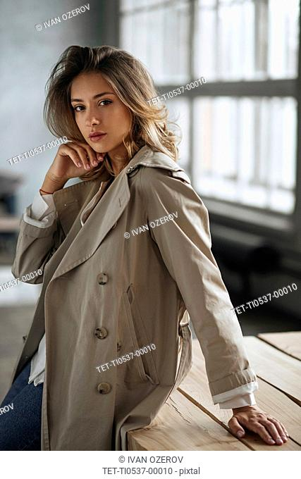 Young woman wearing grey trench coat