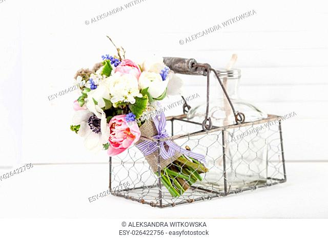 Bouquet from pink tulips, violet grape hyacinths, white anemones, violet veronica and white buttercup with violet ribbon lying in the metal
