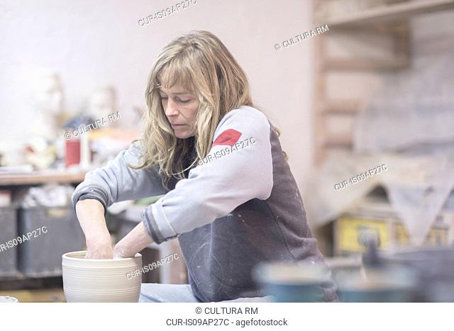 Female potter raising clay pot on pottery wheel