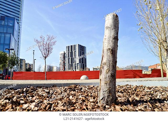 Tree cut, red aluminium wall, fence, buildings, blue sky. Plaça Europa, Plaza Europa, District VII, Gran Via, Hospitalet de Llobregat, Barcelona province