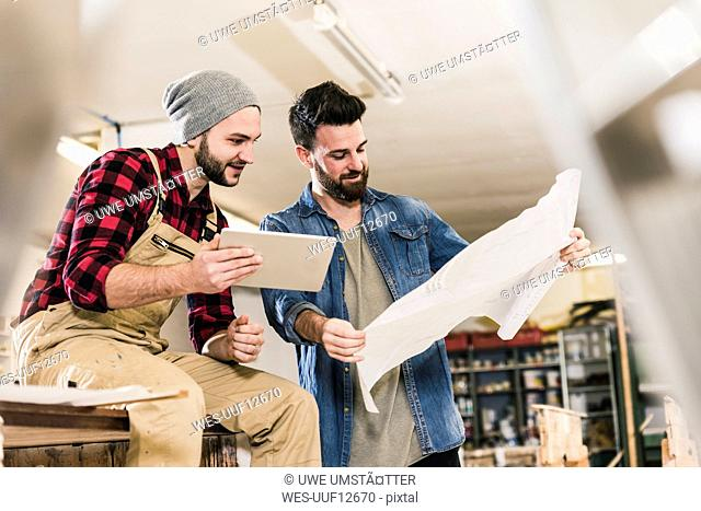 Two men with tablet looking at draft in workshop
