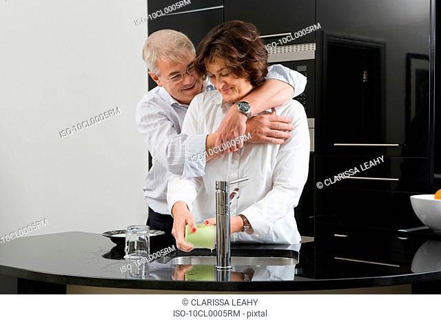 Man hugging woman washing up